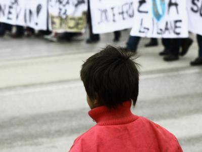 A Roma child looking at protesters